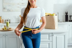 cropped view of happy young woman measuring waist near groceries