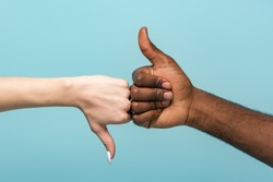 cropped view of interracial couple showing thumbs up isolated on blue
