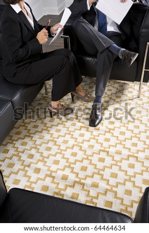 Cropped view of man and woman in business suits talking and reviewing report