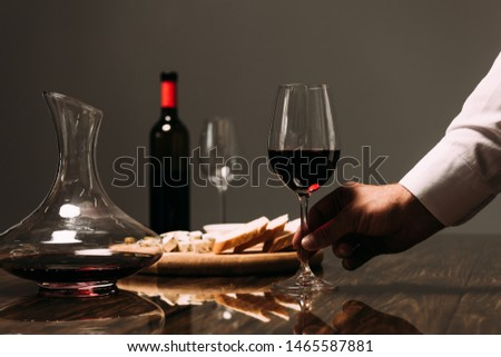 cropped view of man holding wine glass at table in restaurant #1465587881