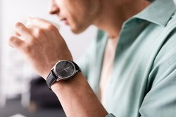 Cropped view of man in wristwatch drinking coffee, concept of time management