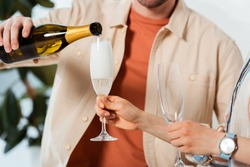 Cropped view of man pouring champagne while woman holding glasses