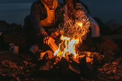 cropped view of man putting log in bonfire near girl