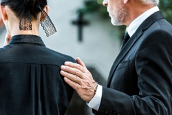 cropped view of man touching woman on funeral