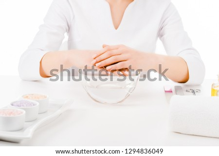 Cropped view of manicurist in uniform doing hand treatment isolated on white #1294836049