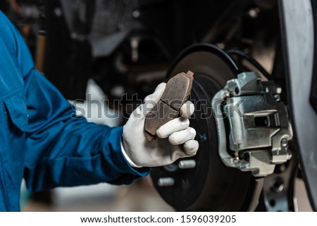 cropped view of mechanic holding brake pad near assembled disc brakes Stockfoto ©