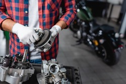 cropped view of mechanic in plaid shirt and gloves holding gearwheel near disassembled motorbike transmission