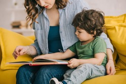 Cropped view of mother and son reading book together