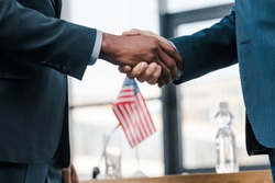 cropped view of multicultural diplomats shaking hands near flag of america