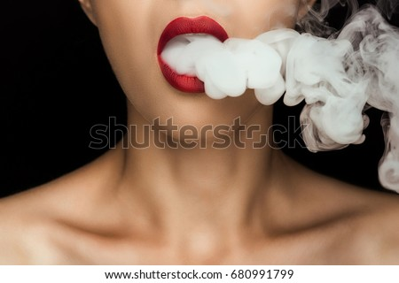 cropped view of naked woman with red lips blowing smoke, isolated on black