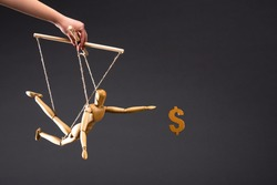 cropped view of puppeteer holding wooden marionette near dollar sign isolated on black