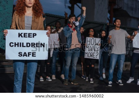 cropped view of redhead girl holding placard with keep children safe lettering near multicultural people on meeting