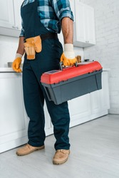 cropped view of repairman in uniform standing and holding toolbox