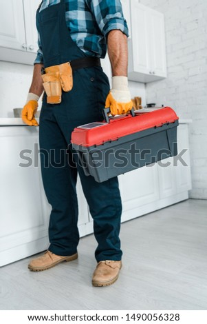 cropped view of repairman in uniform standing and holding toolbox  #1490056328