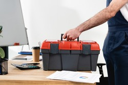 cropped view of repairman with toolbox on office desk with papers and coffee to go