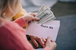 cropped view of senior couple holding envelope with 'roth ira' lettering and dollar banknotes