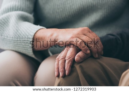 cropped view of senior woman holding hands with retired husband
