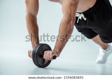 cropped view of sexy muscular bodybuilder with bare torso exercising with ab wheel on grey background