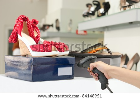 Cropped view of shop assistant scanning code on shoe box. Image with selective focus.