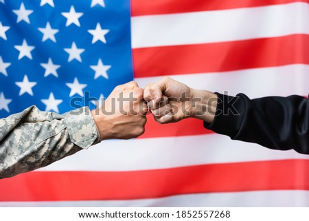cropped view of soldier fist bumping with civilian man near american flag on blurred background ストックフォト ©