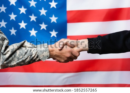 cropped view of soldier shaking hand with civilian man near american flag on blurred background ストックフォト ©