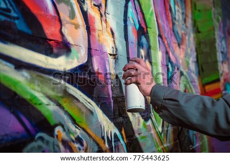 cropped view of street artist painting graffiti with aerosol paint on wall at night #775443625