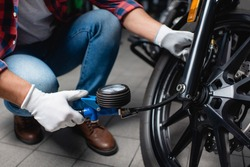 cropped view of technician measuring air pressure in tire of motorbike with manometer, blurred background