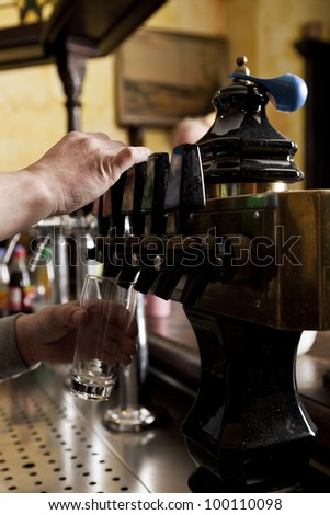 Cropped view of the hands of a barman dispensing drought beer from generator