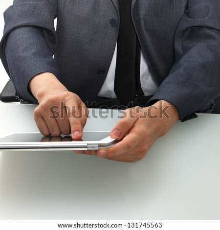 Cropped view of the torso and hands of a man seated at a desk using a tablet computer touching the screen with his finger