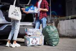 Cropped view of the young open minded family unpacking bags and plastic containers with rubbish from their electro car before the visit to the garbage sorting factory. Garbage recycling concept