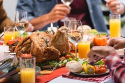 Cropped view of turkey with drinks and candles on table near multiethnic family celebrating thanksgiving