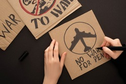 cropped view of woman drawing placard with no war for peace lettering and airplane on black background