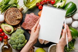 cropped view of woman holding empty notebook above food for ketogenic diet menu