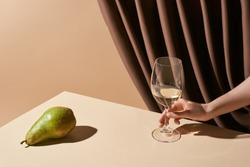 cropped view of woman holding glass of white wine near green pear on table near curtain isolated on beige, still life concept