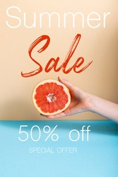 cropped view of woman holding juicy half of grapefruit near summer sale, fifty percent off, special offer lettering on beige and blue