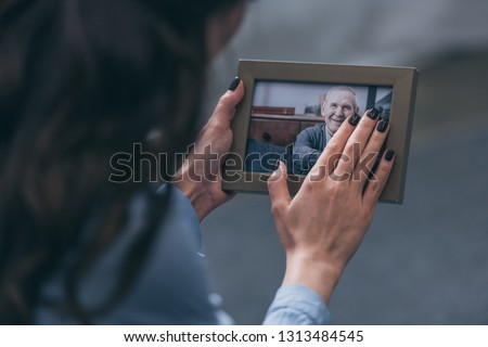cropped view of woman holding photo frame with mature man at home, grieving disorder concept