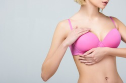 cropped view of woman in pink bra touching breast isolated on grey, breast cancer concept