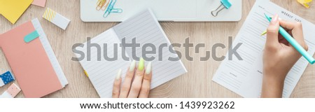 cropped view of woman making notes in weekly list, sitting behind wooden table with notepad and stationery