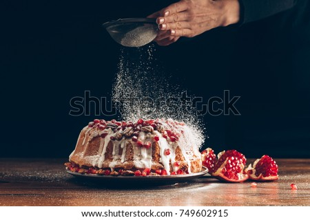 cropped view of woman powdering traditional homemade pomegranate christmas cake with icing sugar
