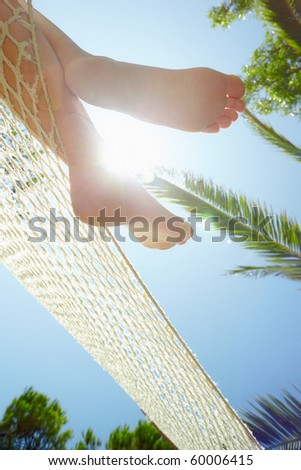 cropped view of woman relaxing on hammock. Low angle view, Vertical shape