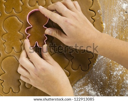 Cropped view of woman's hand using plastic gingerbread cookie cutter on worktop