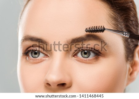 cropped view of woman shaping eyebrow with eyebrow brush isolated on grey