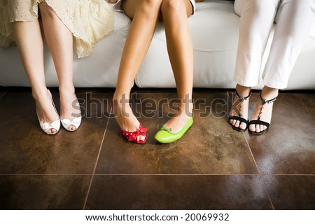 Cropped view of woman wearing mismatched shoes with women in high heels sitting beside
