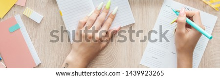 cropped view of woman writing in weekly list, sitting behind wooden table with notepad and stationery