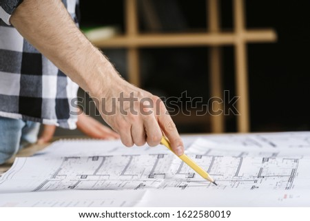 Cropped view of young adult architect working with blueprints in workplace studio, pointing at documents with pencil, choosing solutions for reconstruction house
