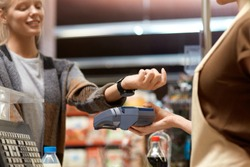 Cropped view of young adult consumer paying for shopping with contactless technology on modern smart watch while cashier holding terminal in hand