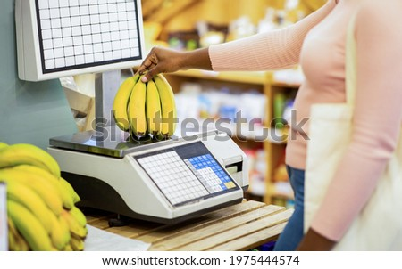 Cropped view of young black woman weighing bananas on scales at supermarket, closeup. Unrecognizable African American lady shopping for food, buying fruits at grocery store Foto d'archivio ©