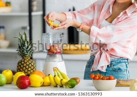 cropped view of young woman adding ingredients in blender  near fruits