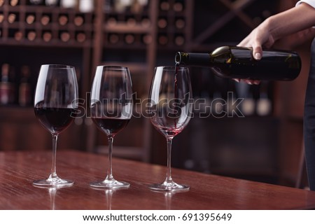 Cropped view sommelier pouring red wine from bottle into glass at table in cellar #691395649
