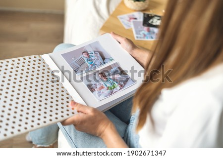 Cropped woman hands holding and watching a family photo album. Mother sit on bed and watching album with little baby son kid boy. Stockfoto ©